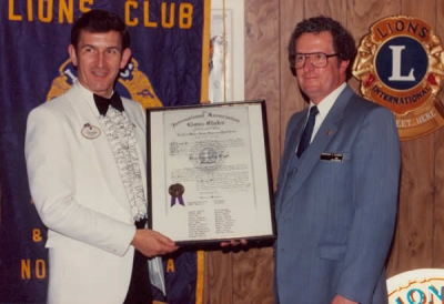 PDG Doug Adams presenting Charter to Lion Reg Harrison.