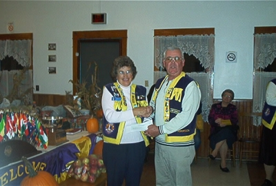 President Florence accepting cheque from Lion John Robertson Windsor & District Lions Club for joint project carried out