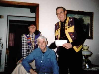 Lion Jim Faulkner and Lion Dallas Moore presenting cheque for $ 1000.00 to Frank Pulsifer to assist with medical expenses