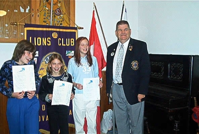 District Governor Earl Einarson presenting Peace Poster Awards to 1st place winner - Alicia Melanson, 2nd place winner - Kelsey Carey and 3rd place winner - Caitlin Cameron.